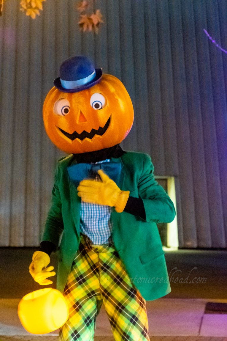 The Pumpkin Man, a friendly scarecrow like figure with a Jack O'Lantern head, topped with a small blue bowler, wearing a green jacket, blue shirt with large blue bowtie, and yellow, black, and green pants.