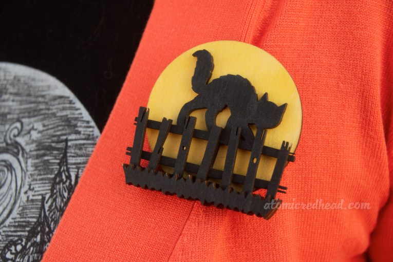 Close-up of my brooch, a black cat stands on a fence against a yellow moon.