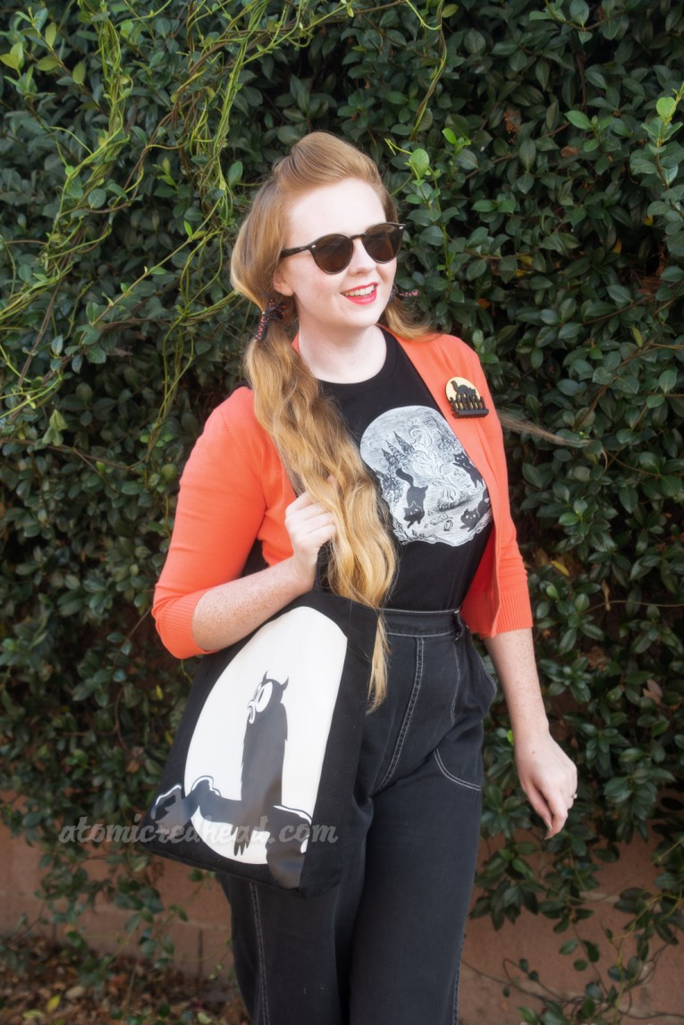 Myself, wearing an orange cardigan over a black t-shirt with a black and white illustration of black cats running around a fire that has spooky ghost cats rising from it, and black jeans.