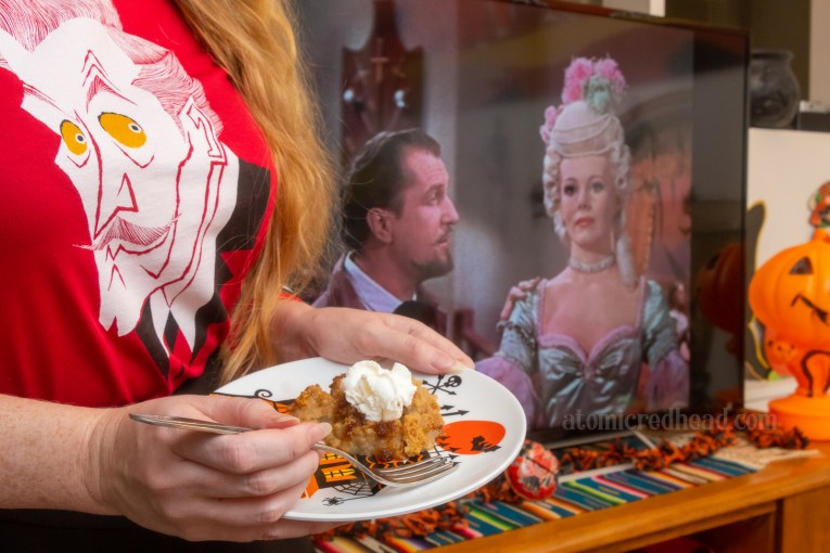 Myself holding a plate with a haunted house illustration on it, with a bit of the Brown Betty on the plate with a dash of whipped cream. In the background is our TV with a scene from House of Wax on the screen, featuring Vincent Price looking at a wax figure of Marie Antoinette.