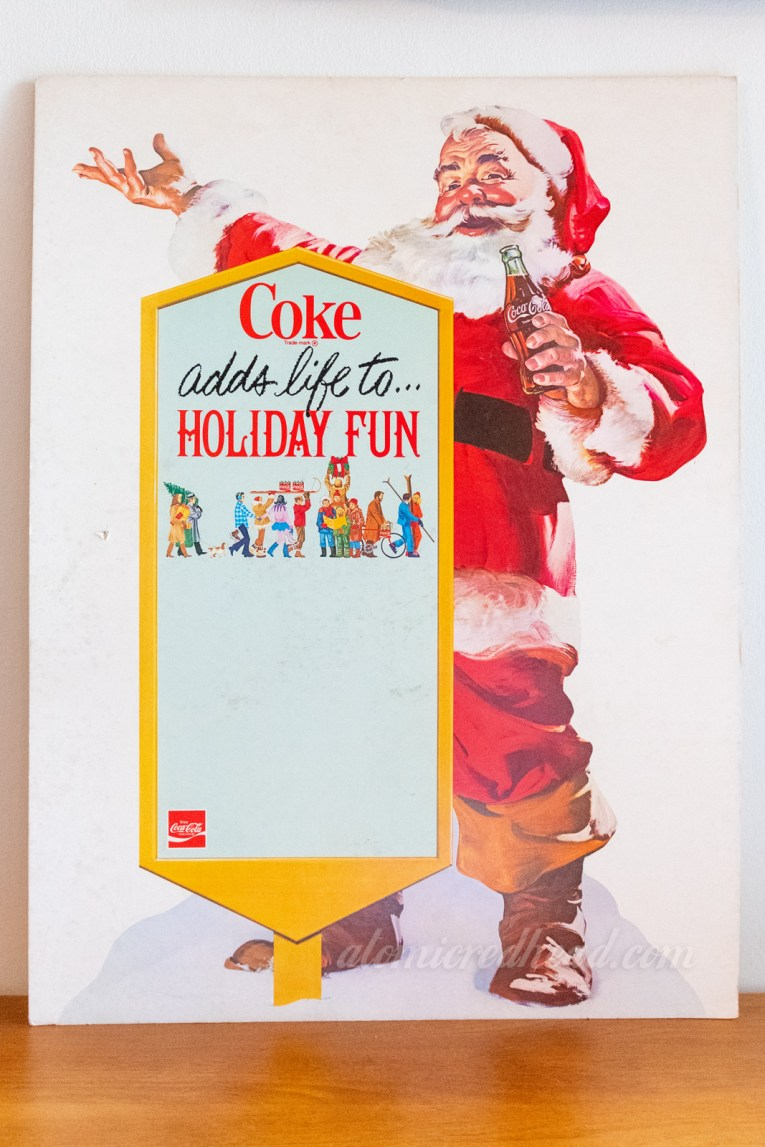 "A cardboard advertisement of Santa next to a sign that reads ""Coke adds life to Holiday Fun"""