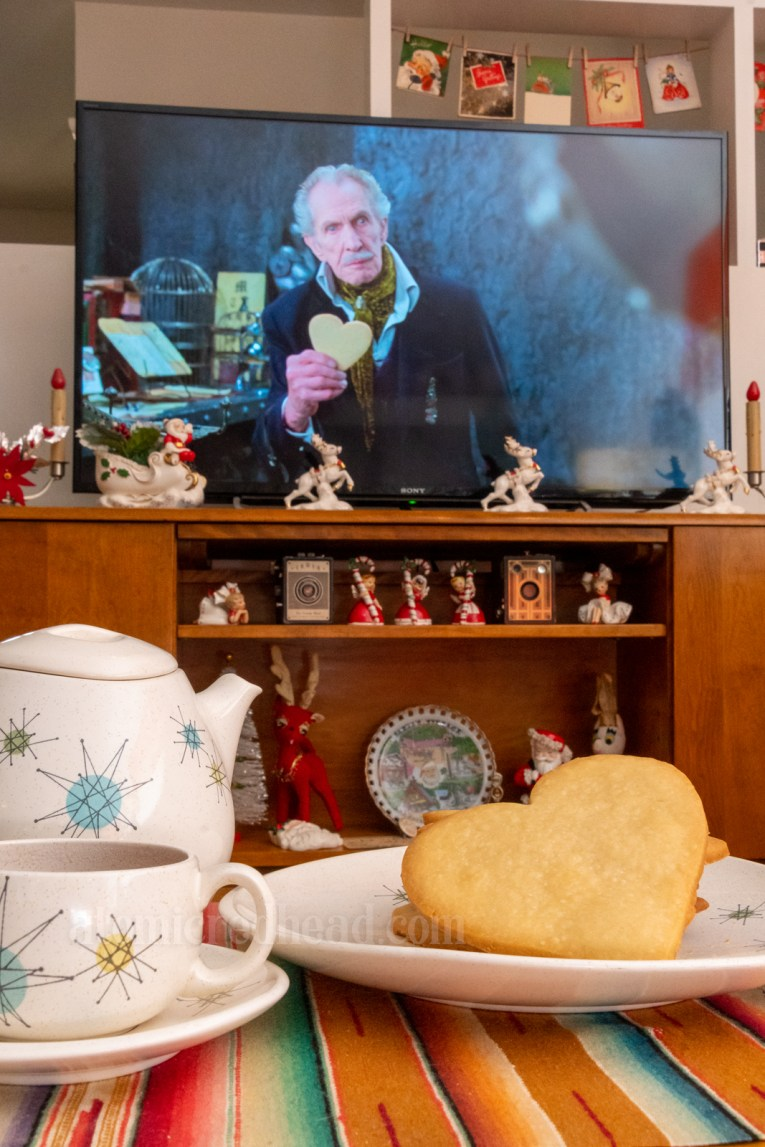 The cookies placed upon a table with a cup of tea next to it, in the background plays Edward Scissorhands with Vincent Price on the screen.