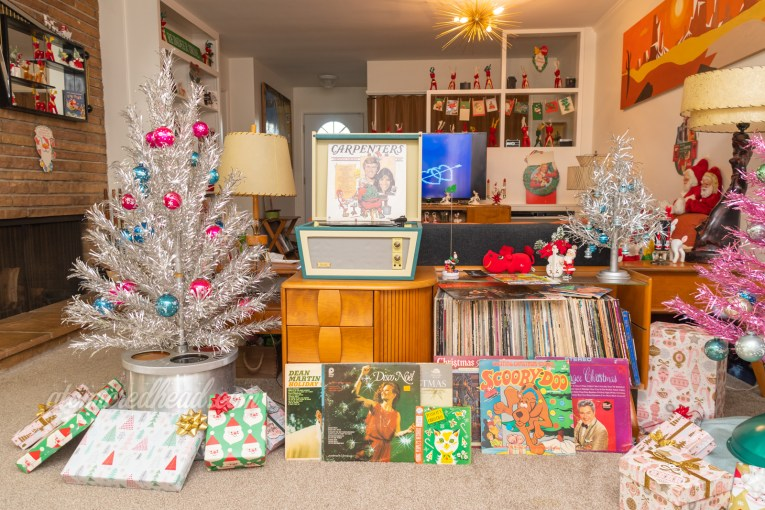 On the left is a three foot silver aluminum tree, sitting in a base that also features a color wheel built in. Next to the tree is a credenza with a record player on top, and a small silver aluminum tree. Various Christmas albums are scattered about.