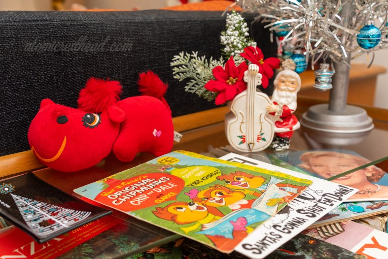 Close-up of a 45 record featuring Chip, Dale, and Clarice. Next to it sits a small red stuffed hippo and a ceramic planter of Santa playing an upright base.