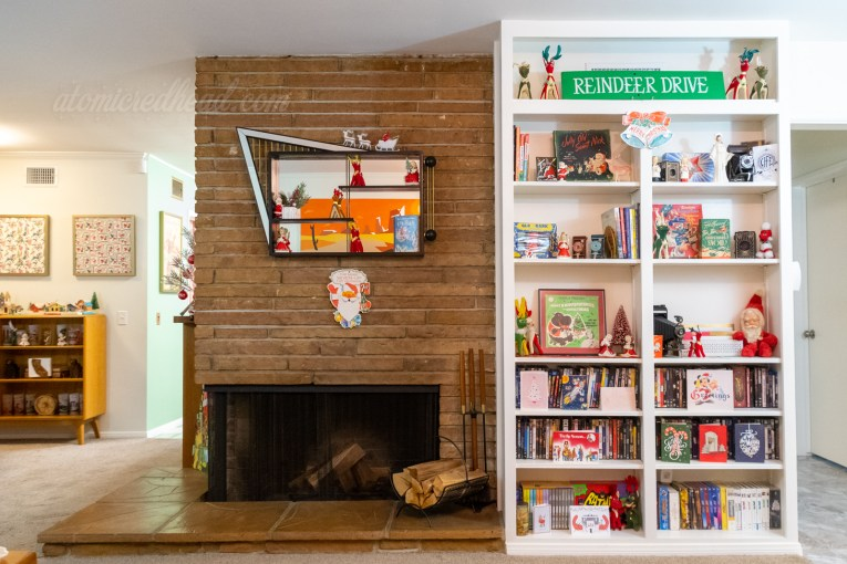 Our fireplace sits on the left, and a built in bookcase is to the right. Various Christmas decorations scatter the shelf.