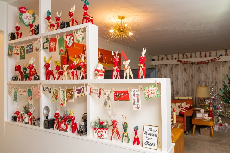 A built in room divider separates the living room from the hallway. In it sits various Christmas decorations, including many small stuffed reindeer, vintage Christmas cards, and ceramic planters of Santa.