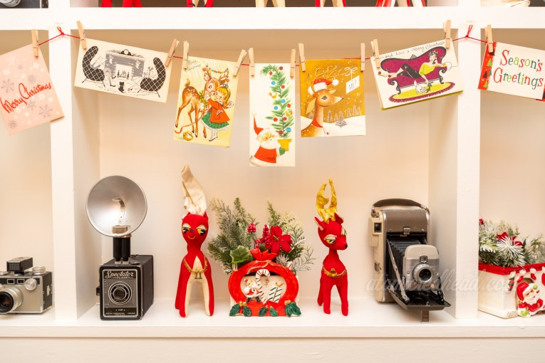 A grouping of vintage Christmas cards hang from the room divider, below are two stuffed reindeer of red fabric, a ceramic planter of Santa and two vintage cameras.