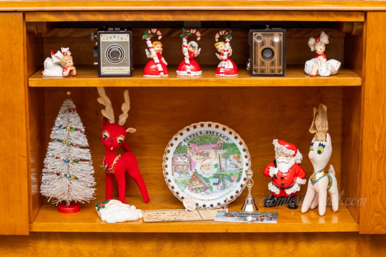 Shelf of our entertainment center, which features three ceramic figures of women holding large candy canes, a white bottle brush tree, a red stuffed reindeer, a decorative plate from Santa's Village, a ceramic figure of Santa, and a white stuffed reindeer.