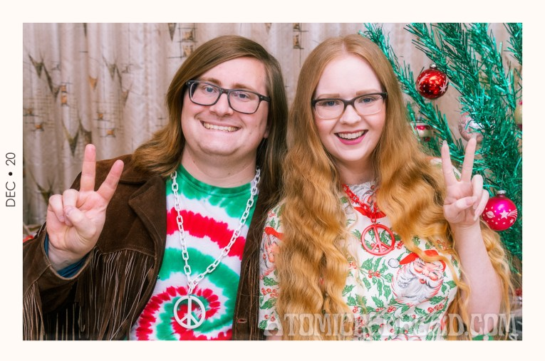 Patrick sits to the left wearing a red, green, and white spiral tie dye shirt, with a dark brown fringe leather jacket over, and a white peace sign necklace, I sit next to him wearing a dress featuring a pattern of Santa and holly, we both are holding our hands in the peace sign.