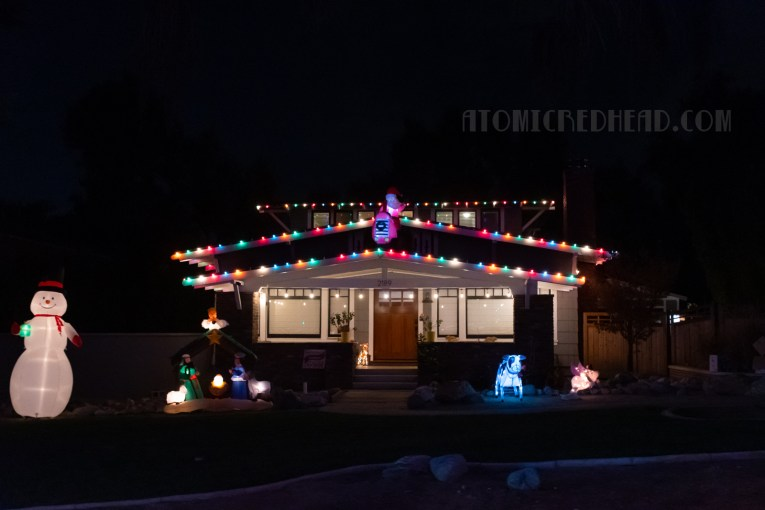 A craftsman style home with lawn decor of Santa on a tractor, snowman, and nativity.