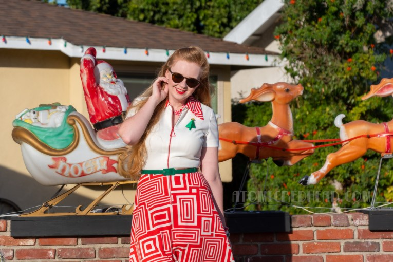 Myself, standing in our front yard with our vintage blow mold Santa and sleigh with reindeer displayed, wearing a red and white 70s dress, with a Christmas tree brooch, green belt, and red shoes.