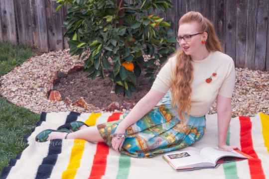 Sitting on a blanket in front of my orange tree, wearing a white sweater, with two orange brooches, and a skirt featuring various California landmarks, while reading.