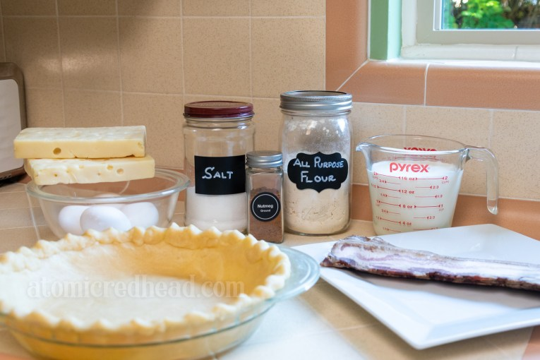 Ingredients, including a pie shell, cheese, eggs, salt, nutmeg, flour, milk, cream, and bacon.