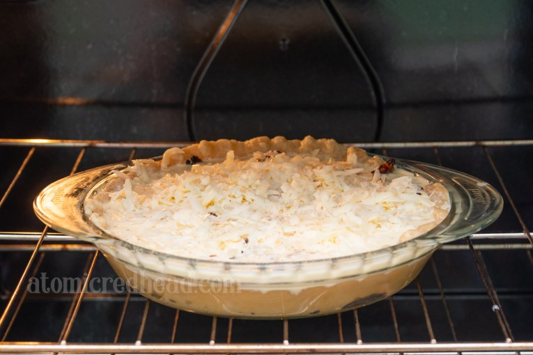 Unbaked quiche placed in the oven.