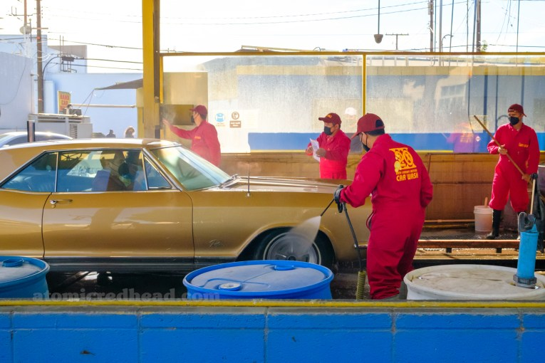 "A gold Buick Rivera enters the car wash, employees in red coveralls with yellow text reading ""20th Century Motors"""