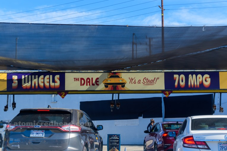 "Banner across the entrance to the car wash, ""3 Wheels, The Dale 'It's a Steal' 70 MPG"""