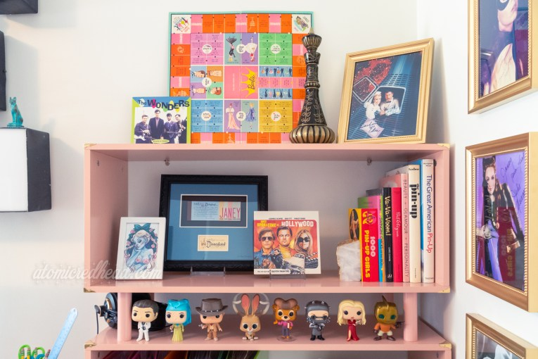 Shot of my bookcase. Various autographs hang on the wall, a collection of Funko Pops sit on the shelf along.