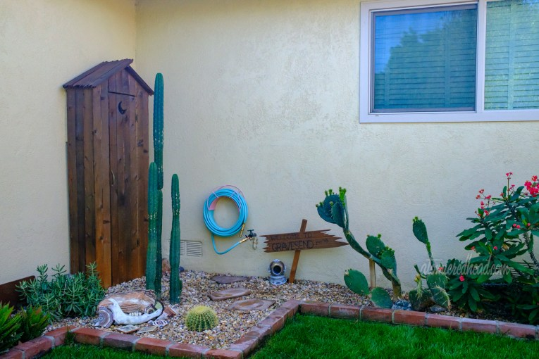 "A corner of the backyard features a faux western style outhouse, cacti, a turquoise garden hose, a dilapidated sign reading ""Welcome to Gravesend"" with a miniature diver helemt."