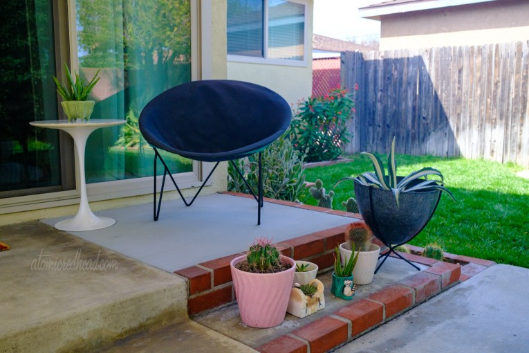 A circular chair with black and turquoise cover sits near the sliding glass door with various planters filled with cacti and succulents nearby.