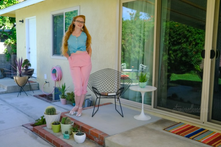 Myself, wearing a turquoise sleeveless top and pink peddle pushers, standing next to the diamond chair.