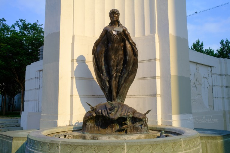 A statue of a woman who rides a small wave with flying fish emerging from it.