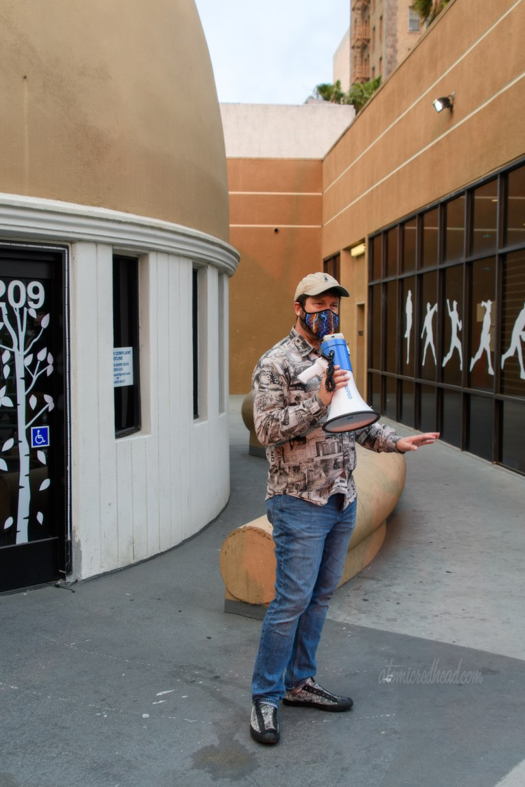 Eric uses a megaphone to talk to those of us on the tour, he wears a shirt made of black and white images of neon signs. Behind him is the old Brown Derby, at his feet includes the brim of the hat.
