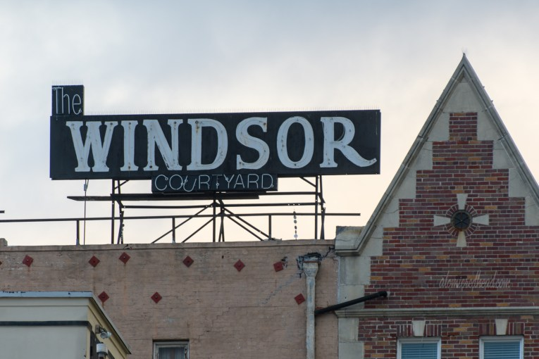 """Atop an old English style brick building is a neon sign reading """"The Windsor Courtyard"""""""