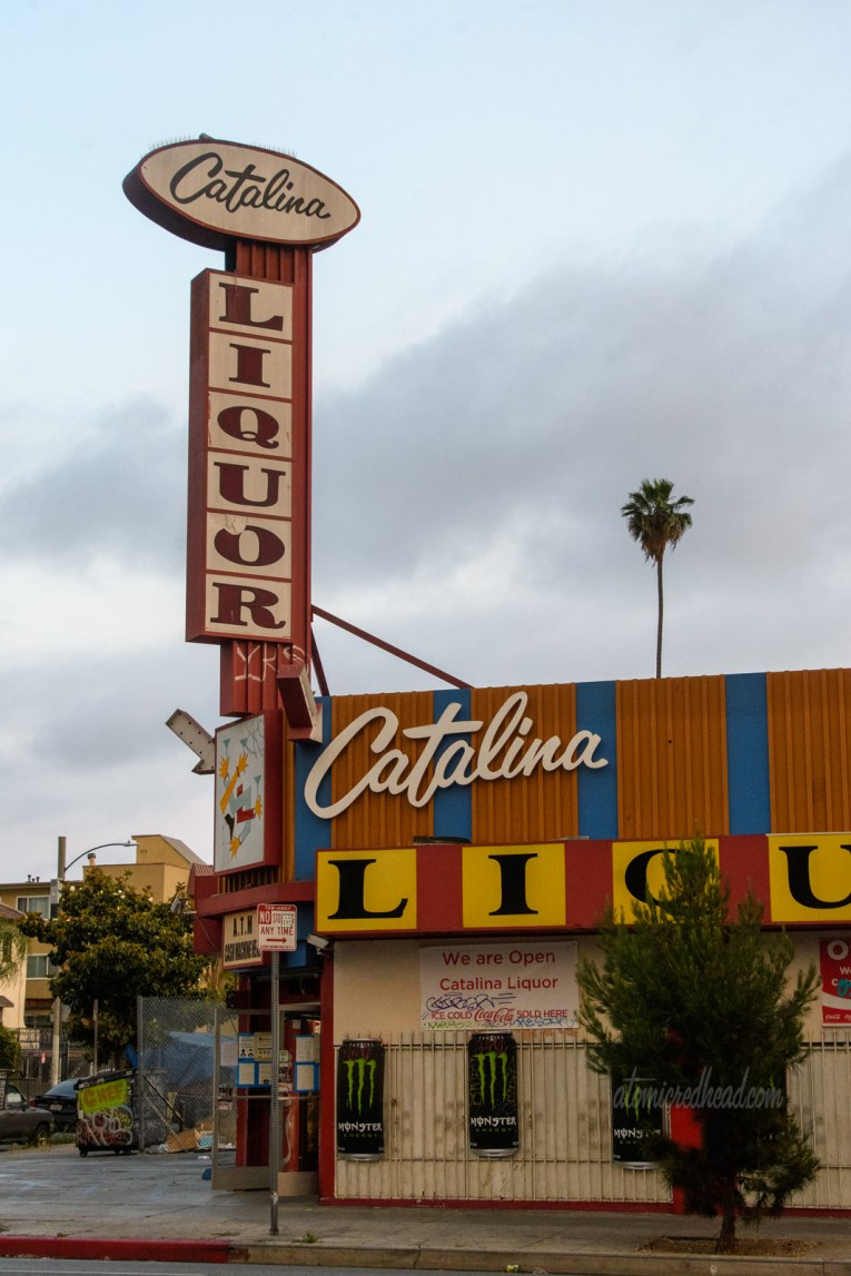 The backlit plastic signs of Catalina Liquor. Catalina is spelled out in an elegant script, while Liquor is spelled out in large yellow blocks with black letters.