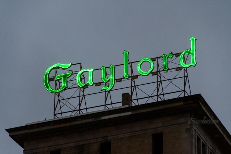 """Gothic letters of green neon spell out """"Gaylord"""" atop a building."""