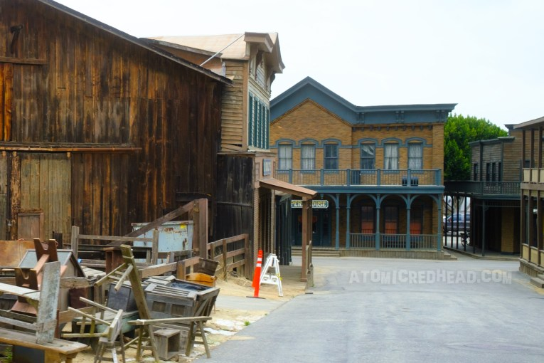 Six Points as it appears today. Weathered western buildings, some feature faux brick. Piles of props are on the left.