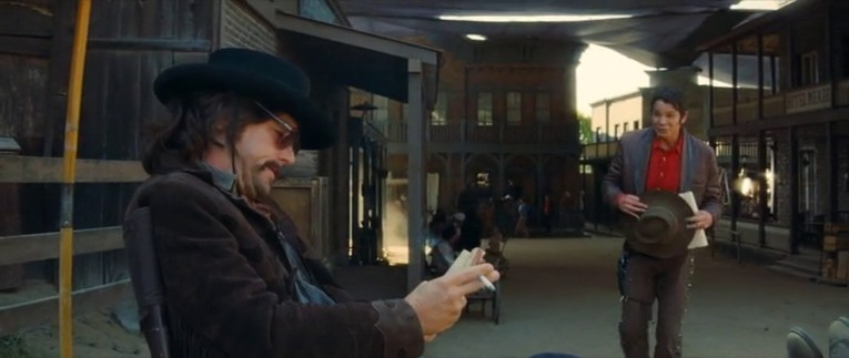 Six Points as it appears in Once Upon a Time in Hollywood. Leonardo DiCaprio sits in a chair dresses as a cowboy on the left, a western town resides just past him.