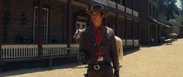 Timothy Olyphant, dressed as a cowboy films a scene for Lancer, a grey stone building with maroon trim is behind him.