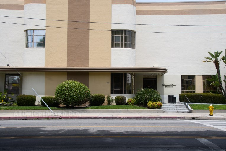 """A tan and cream streamline moderne building reads """"Paramount Pictures Studio Tour"""" in small script by a door."""