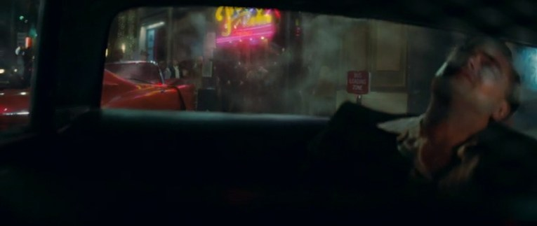 Rick sits in the back of a police car, through the back window you see a wreck pink Cadillac in front of the Frolic Room, whose sign is lit up with yellow and pink neon.
