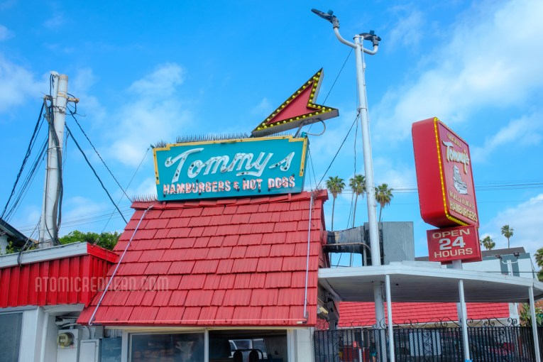 """The iconic red roof of the original shack, with a small blue sign with a red arrow atop it. Script reads """"Tommy's Hamburgers & Hot Dogs"""""""