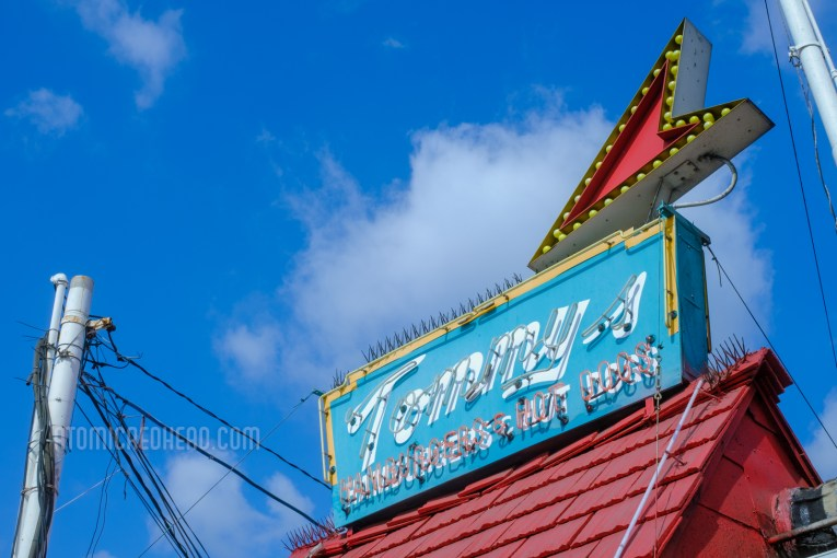 """Angled view of the neon atop of the red roof reading """"Tommy's Hamburgers & Hot Dogs"""""""