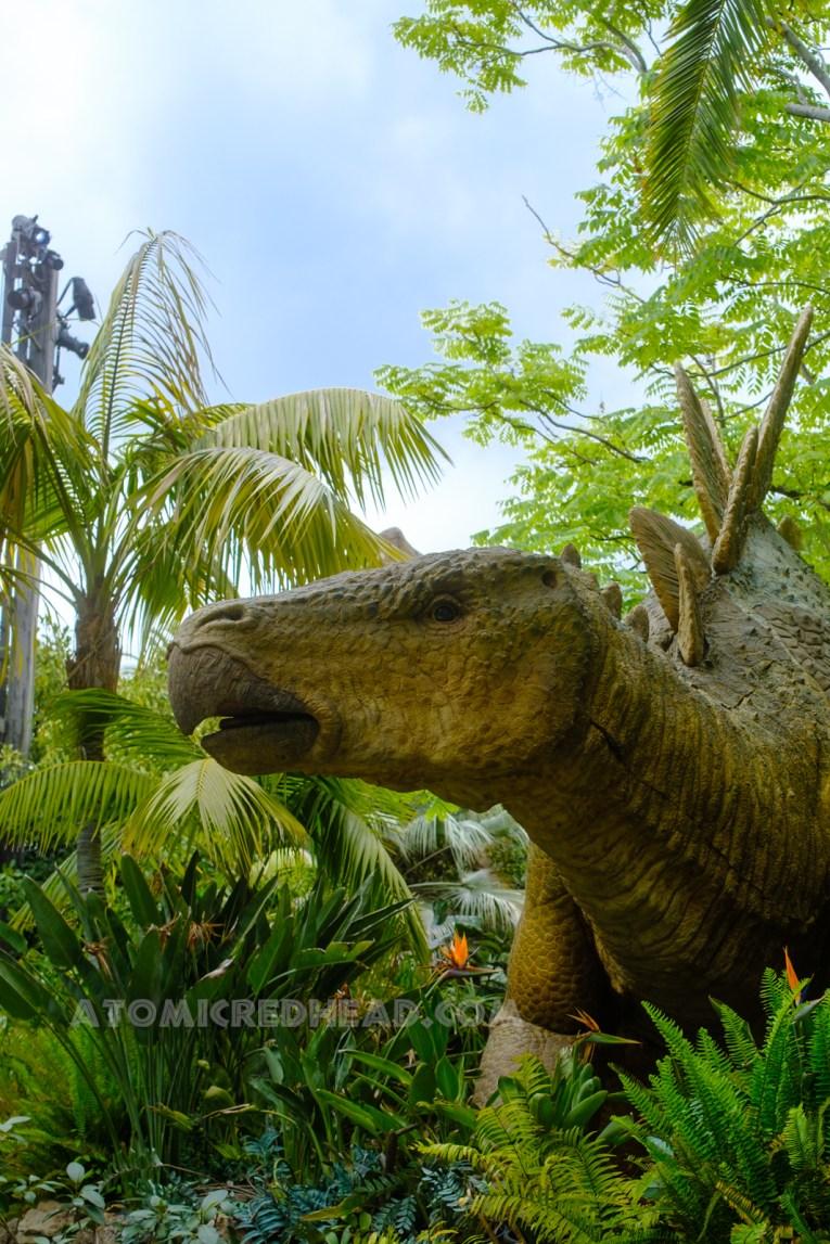 A greet stegosaurus peeks from lush green foliage.