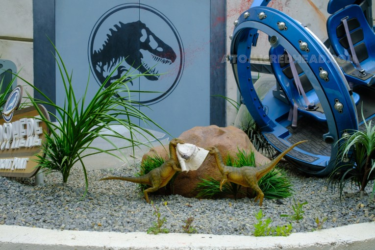 Two compsognathus fight over a khaki hat with the Jurassic World logo embroidered on it. A broken gyrosphere sits to the right.