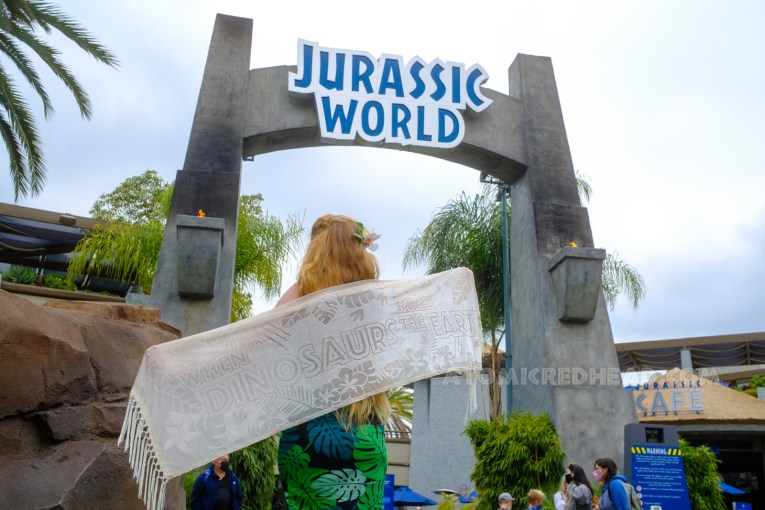 """Myself standing in front of the entrance to the Jurassic World ride, my back to the camera holding my shawl out wide. The shawl is white with various tropical leaves on the edge and text reading """"When Dinosaurs Ruled the Earth"""" The grey stone arch for Jurassic World is above me with blue text reading """"Jurassic World"""""""