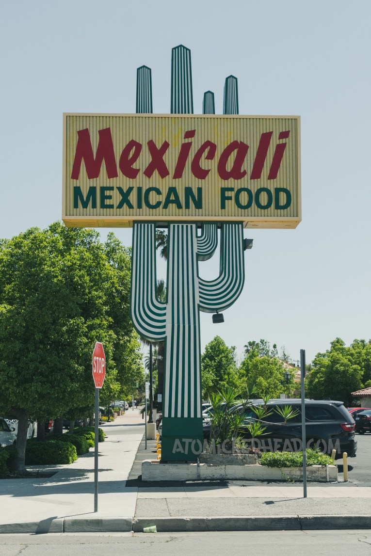 """A large backlit plastic cactus rises toward a blue sky. A yellow rectangle crosses the cactus reading """"Mexicali Mexican Food"""""""
