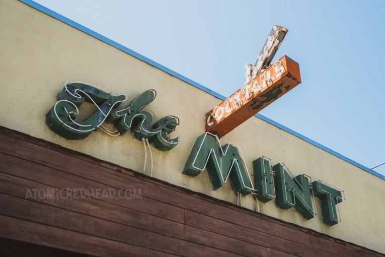 """Green neon letters reading """"The Mint"""" are attached to the side of a stucco building. A small red sign juts out from the building reading """"Cocktails"""" and features a small arrow above."""