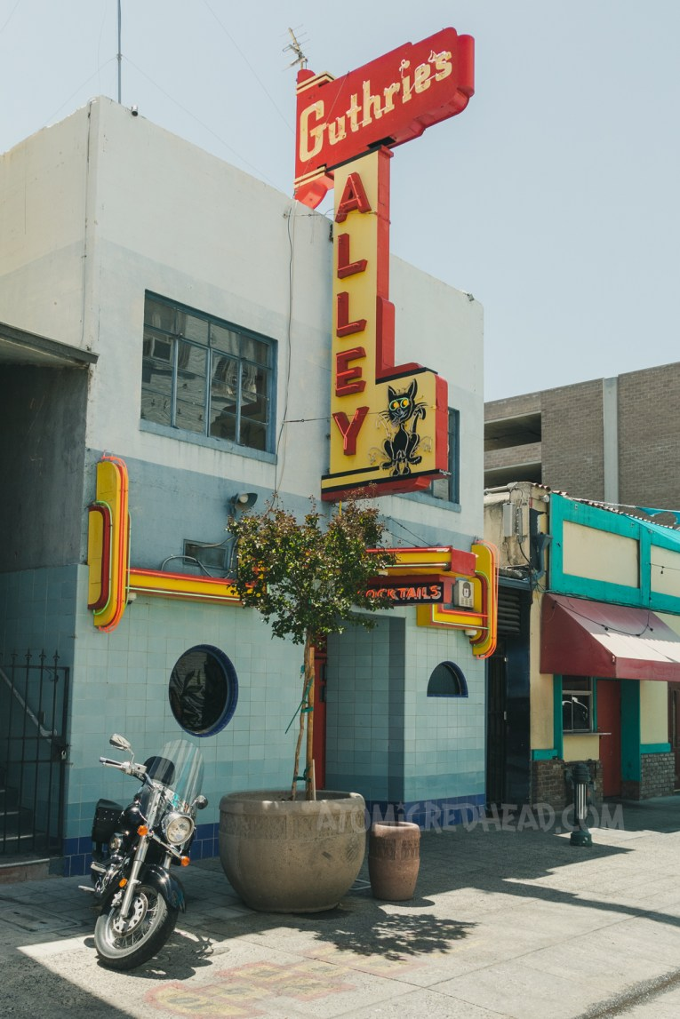 """Guthrie's Alley Cat, a small Art Deco style building. The lower half is made up of blue tiles. A neon sign of red and yellow reads """"Guthrie's Alley"""" and then features a small black cat."""