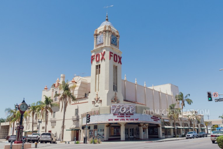 """The Fox Theatre, an elegant Spanish Colonial Revival style building with a tall clock tower at its corner, with red letters spelling """"Fox"""" an Art Deco marque curves around the corner with script reading """"Fox"""" in neon."""