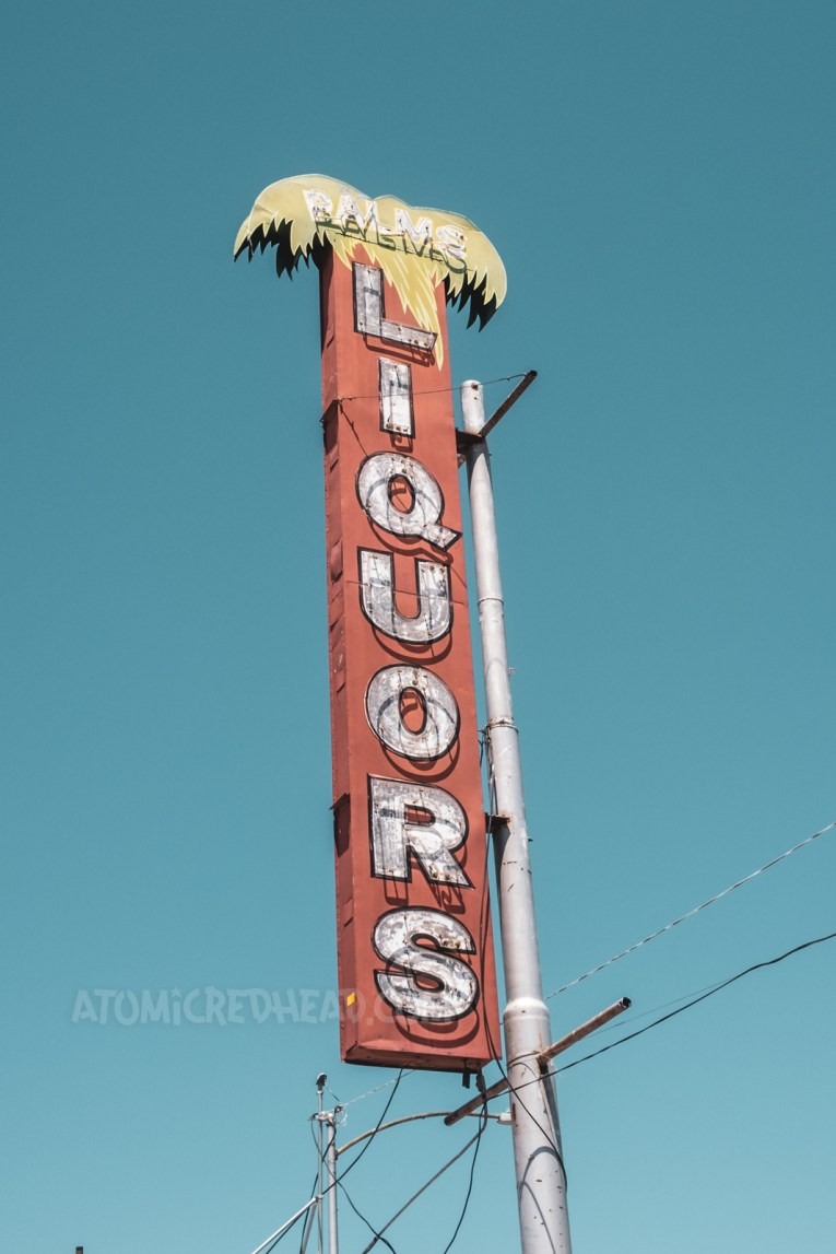 """A red neon sign features a palm tree at the top. Letters spell out """"Palms Liquors"""""""