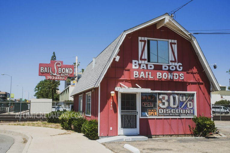 """A red barn style building with white trim reads """"Bad Dog Bail Bonds"""" just past the building is a red and white neon sign reading """"Bail Bond Leon"""""""