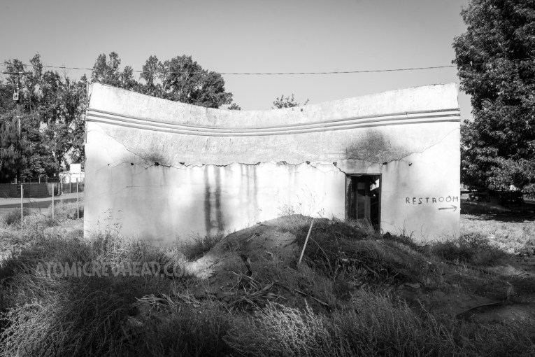 An abandoned and overgrown garage building with the top portion leaning backwards, about to collapse on itself.