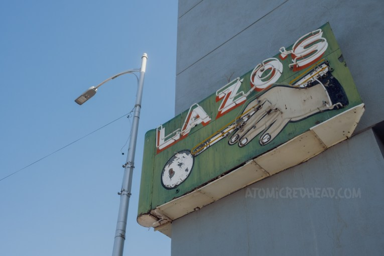 """Neon sign on the corner of a building reading """"Lazo's"""" and features a hand aiming a billiard cue at a ball."""