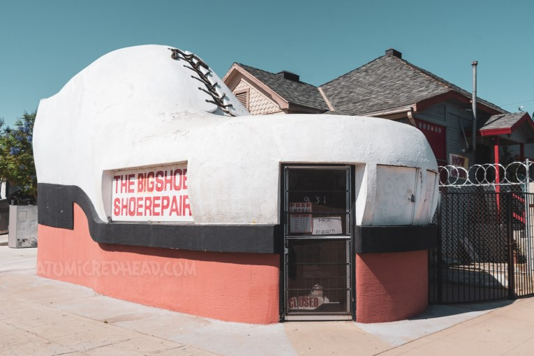 A shoe repair shop that is shaped like a gigantic shoe, complete with laces at the top.