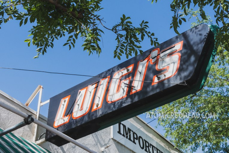 """A small red, white, and black neon sign simply reads """"Luigi's"""""""