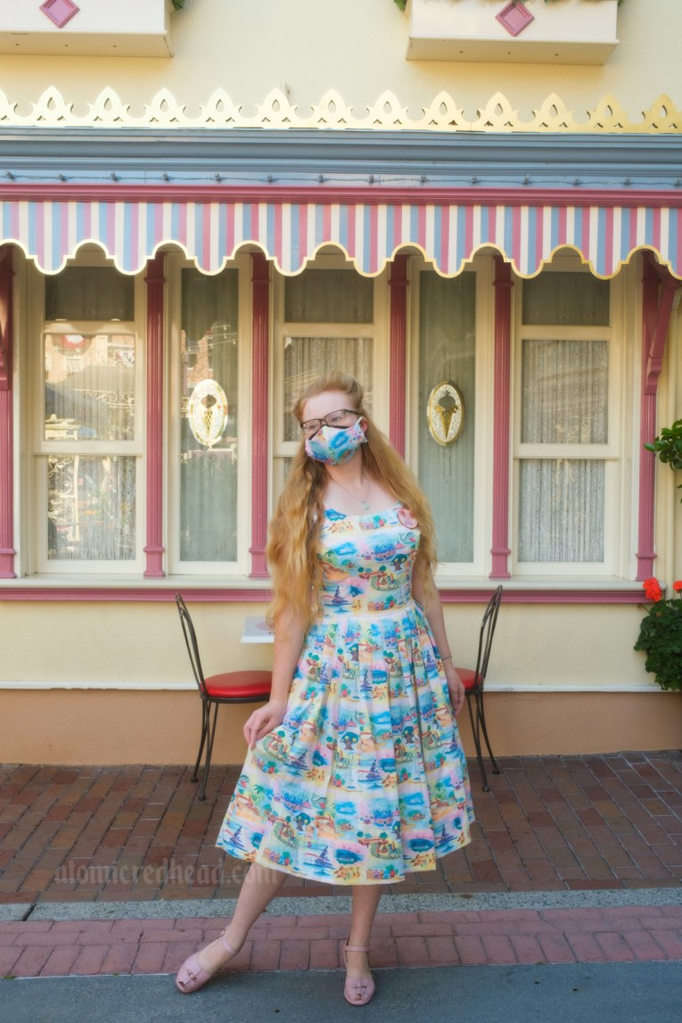 Myself standing along Main Street USA, wearing a sun dress featuring various icons of Disneyland printed on it, including Sleeping Beauty Castle, the Matterhorn, a rocket, and more.